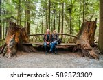Couple Sitting On Bench Made...