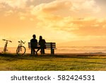couple sitting on park bench... | Shutterstock . vector #582424531