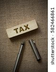 tax on wooden block on a brown... | Shutterstock . vector #582466861