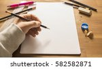 hand holding pencil over white... | Shutterstock . vector #582582871