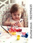 Small photo of girl 1-year self-plays with the paint,the first acquaintance with the works