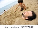 Playing with sand and digging the father in - stock photo
