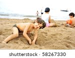 Playing in sand on beach - stock photo