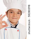 Cute young boy dressed in chef clothes doing and ok sign - stock photo