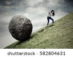 Stock photo image of young businesswoman climbing on the hill while pulling big stone with a chain 582804631