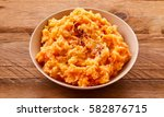 Small photo of Mixture of orange pureed carrot and potato in a bowl on a rustic wooden background for use as a cooking ingredient or to serve as an accompaniment to a meal