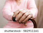 old woman hands with cane.... | Shutterstock . vector #582911161