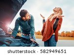 Couple on the road having problem with a car. Broken down car on the road. - stock photo
