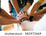 group of people joining hands... | Shutterstock . vector #582972469