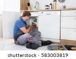 male plumber fixing sink pipe... | Shutterstock . vector #583003819
