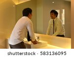 An Asian Man Washing Hands In...