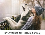 Stock photo image of young girl with her dog alaskan malamute outdoor at autumn or winter domestic pet husky 583151419
