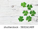 Small photo of Saint Patricks Day background with green shamrock on white wooden texture top view.