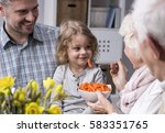 Small photo of Grandmother feeding with healthy carrots grandchild sitting on her father's lap