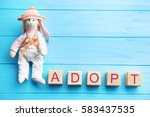 Small photo of Bunny toy and cubes with word ADOPT on wooden background