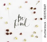 Small photo of Minimalistic composition with words Be Kind written in calligraphic style on paper with wildflower buds on white background. Flat lay, top view