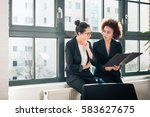 two young female colleagues... | Shutterstock . vector #583627675