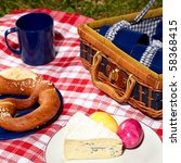 picnic cloth with basket and food on it - stock photo