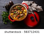 Small photo of Beef meat stewed with potatoes, carrots and spices in cast iron pan on burned black wooden background