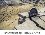 Small photo of round circle black clock stand on cracked dry soil in desert land. apocalypse, ecological catastrophe in nature. global warming. Environment,Concept. lost time is money