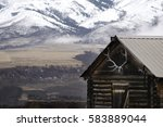 Old cabin with snow covered mountains in background and elk antlers - stock photo