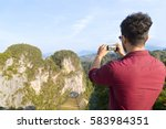 young man mountains take photo... | Shutterstock . vector #583984351