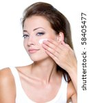 Beautiful woman applying moisturizer cosmetic cream on face - on a white - stock photo