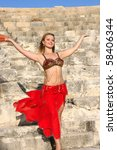 Beautiful belly dancer in red on the ancient stairs of Kourion amphitheatre in Cyprus. - stock photo