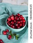 Small photo of Red cranberries in a blue bowl. Ripe berries of Vaccinium macrocarpon, also large cranberry, American cranberry or bearberry.