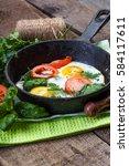 breakfast with fried eggs on pan | Shutterstock . vector #584117611