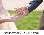 closeup of the groom putting a... | Shutterstock . vector #584145901