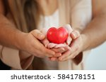 young couple holding small red... | Shutterstock . vector #584178151