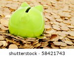 Green piggy bank and sea of  gold money - stock photo