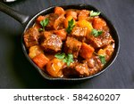 Small photo of Beef stew in frying pan on black background, close up view