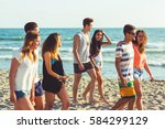 Small photo of Multiracial group of friends walking on the beach. There are four girls and three boys, wearing trunks and colourful t-shirts. Color filter applied