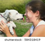 Small photo of white puppy lick girl lips close up summer portrait