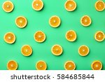 Stock photo colorful fruit pattern of fresh orange slices on green background from top view 584685844