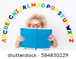 Small photo of Happy preschool child learning to read and write playing with colorful roman alphabet letters. Educational abc toys and books for kids. School student doing homework. Kid reading in kindergarten