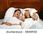 Couple in bed while the woman is trying to sleep and the man is snoring - stock photo