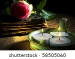 old book with rose and three candles on old table with mystic lightning - stock photo