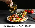 female hand pouring oil over... | Shutterstock . vector #585152815