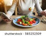 woman eating salad  | Shutterstock . vector #585252509