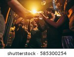 Stock photo low angle shot of group of friends enjoying drinks at bar together young people at nightclub 585300254