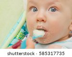 mother feeding baby food to... | Shutterstock . vector #585317735