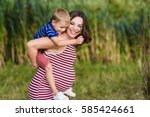 child sitting on the shoulders... | Shutterstock . vector #585424661