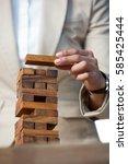 business man placing wooden... | Shutterstock . vector #585425444