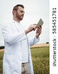 Small photo of Agronomist using digital tablet in the field on a sunny day