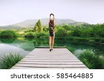 Stock photo young woman stands on a wooden bridge with raised arms up on the nature background travel freedom 585464885