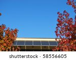 Solar panels on the roof against blue sky in autumn, free copy space - stock photo