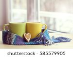 two mugs tied a warming scarf... | Shutterstock . vector #585579905
